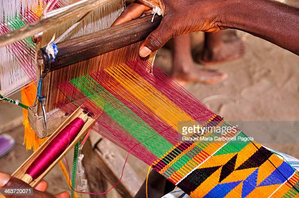 Man weaving kente textile stripe using a traditional loom