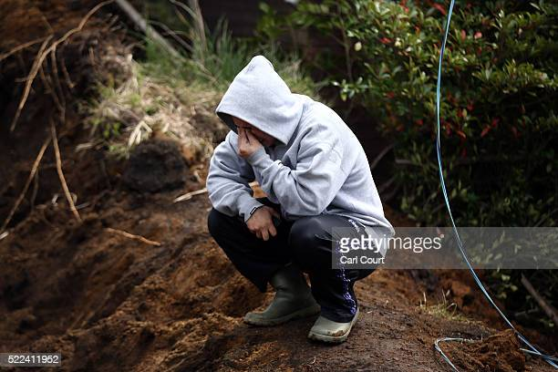 Man weeps as rescue workers search for a body in a house that was destroyed by a mudslide following an earthquake, on April 19, 2016 in Minamiaso...