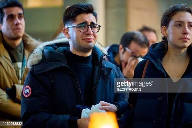 Man weeps during a service at Western University in London, Ontario on January 8, 2020 for the four graduate students who were killed in a plane...