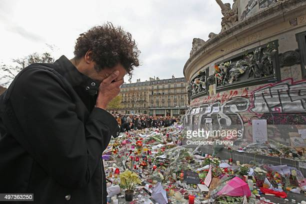 A man weeps for a lost friend as people gather to observe a minutesilence at the Place de la Republique in memory of the victims of the Paris terror...