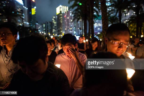 Man weeps while holding a candle during a candlelight vigil at Victoria Park in Hong Kong, to mark the 30th anniversary of the 1989 Tiananmen...