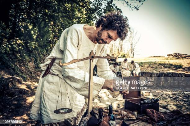 Man weighing coins and precious metals on a scale, replica of a Carolingian village, Archeodromo di Poggibonsi, Italy, 9th-10th century. Historical...