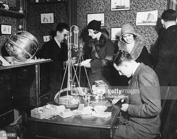 A man weighing gold after the lifting of the Gold Standard encouraged people to sell their gold jewellery and ornaments