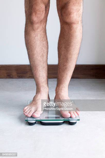 man weighing self on bathroom scale - fat legs stock photos and pictures