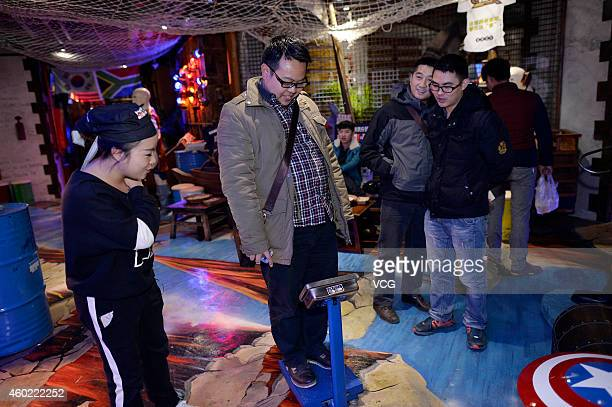 A man weighs himself at a restaurant on December 9 2014 in Chongqing China A restaurant in Chongqing is giving discounts on meals depending on the...