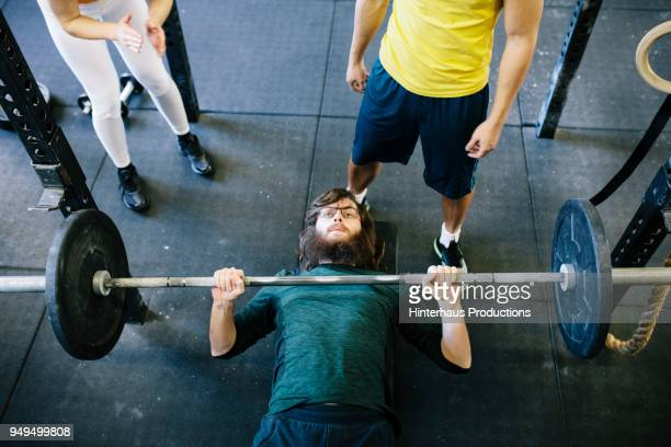 man weightlifting at gym with friends - lying on back stock pictures, royalty-free photos & images
