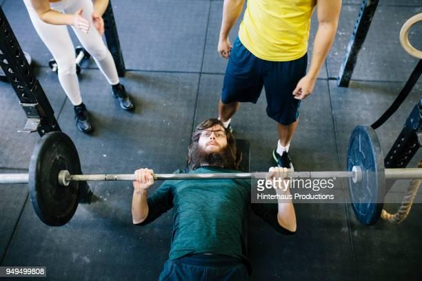 man weightlifting at gym with friends - deitado de costas - fotografias e filmes do acervo