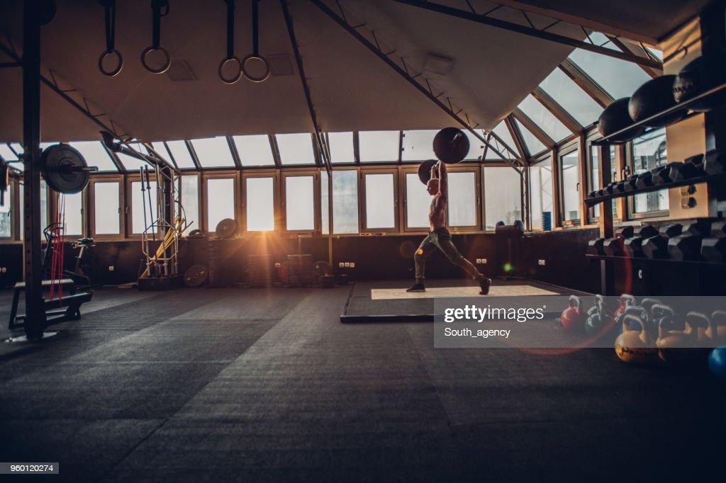 Mann Gewichtheben im Sonnenuntergang : Stock-Foto