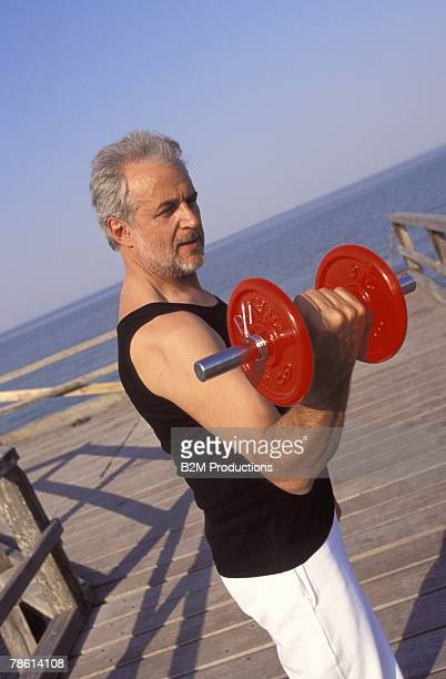 Man weightlifting on boardwalk
