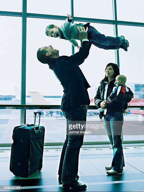Man welcoming family on the airport and holding son