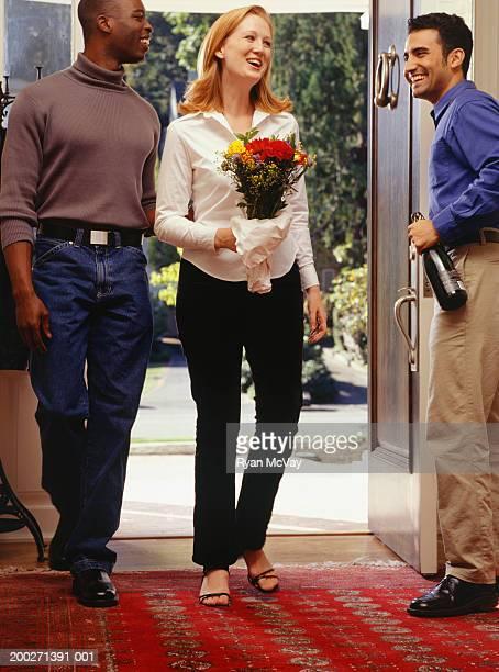 Man welcoming friends at front door into home