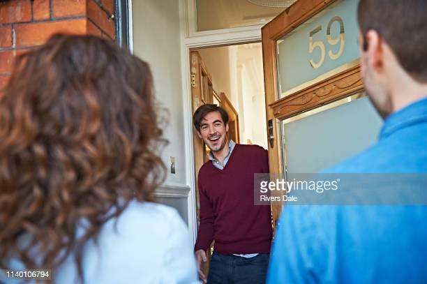 man welcoming friends at front door - bezoek stockfoto's en -beelden