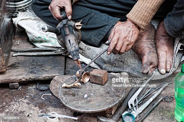 Man, welder, soldering bronze at his street stall on the streets of Varanasi, Benares, Uttar Pradesh, India