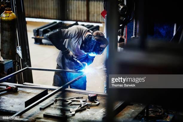 Man welding corner of metal frame in workshop