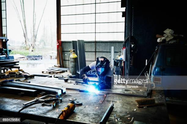 Man welding frame at bench in metal workshop