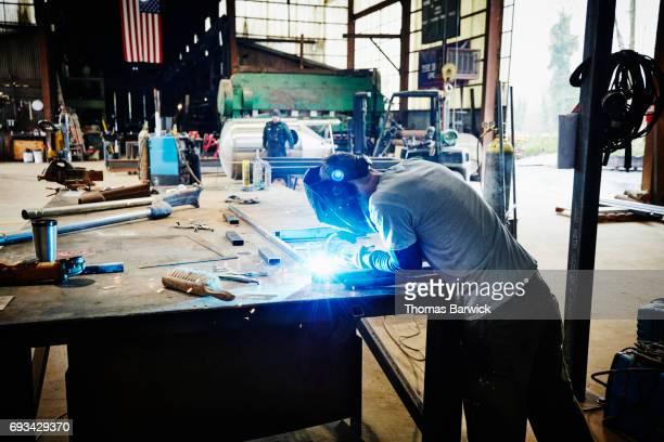 Man welding frame in metal workshop