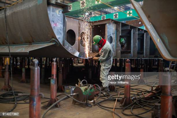 a man welding inside a shipbuilding factory - shipyard stock pictures, royalty-free photos & images