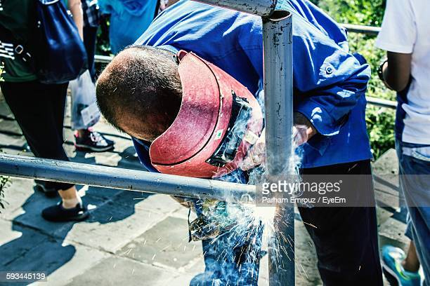 man welding rods on footpath - parham emrouz stock pictures, royalty-free photos & images