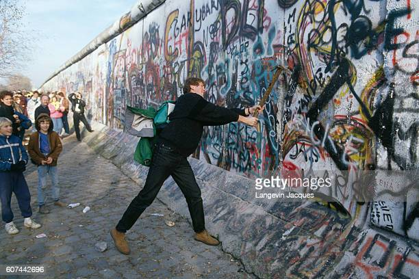 A man welds a pickaxe to participate in the destruction of the Berlin Wall between the Postdam Platz and the Brandenburg Gate The Berlin Wall...