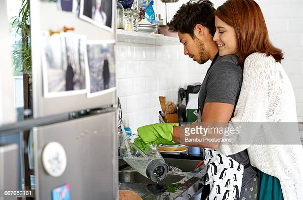 Man whashing dishes and woman embracing