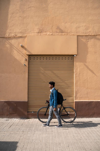 Man wheeling bicycle by wall during sunny day