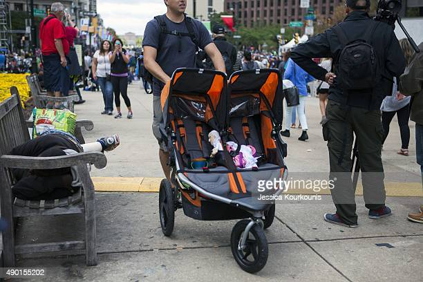 A man wheels a double stroller holding a stuffed version of Pope Francis while people wait to see his motorcade and attend the Festival of Families...