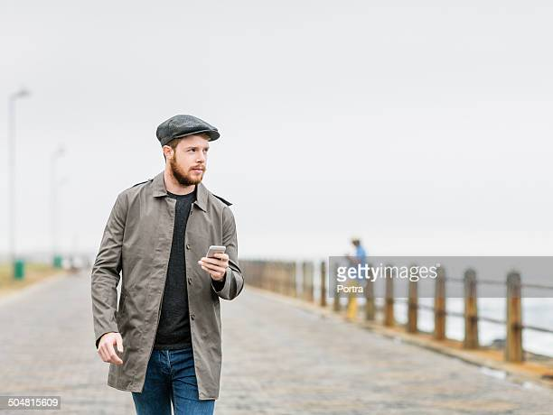 man while walking on footpath at seaside - flat cap stock pictures, royalty-free photos & images