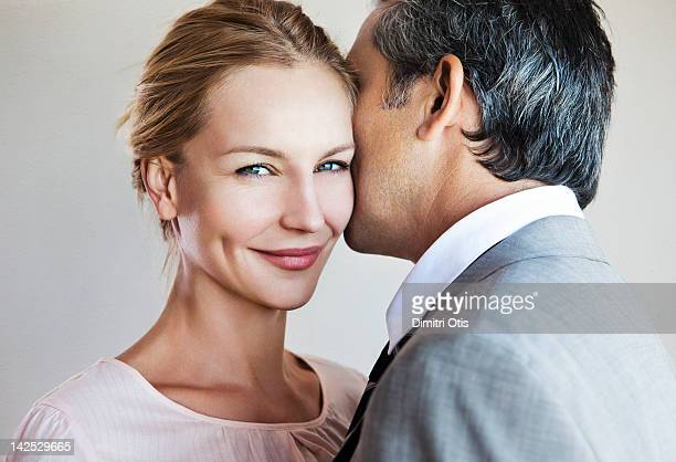 man whispering to smiling woman - elegante kleidung stock-fotos und bilder