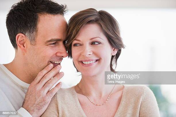 man whispering to womans ear - gossip stock pictures, royalty-free photos & images