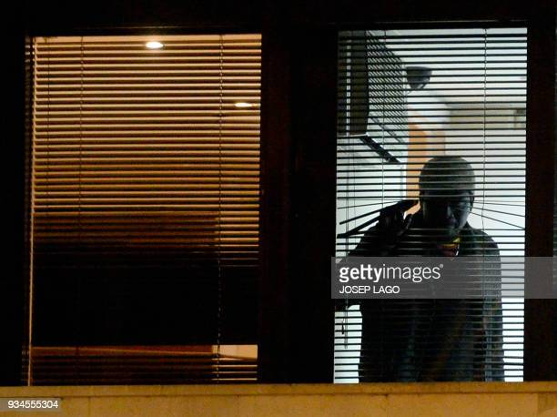A man who allegedly has taken the wife of Mali's honorary consul hostage looks through a window of the consulate of Mali in Barcelona on March 19...