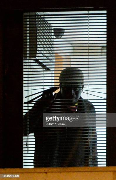 A man who allegedly took the wife of Mali's honorary consul hostage looks through a window of the consulate of Mali in Barcelona on March 19 2018...