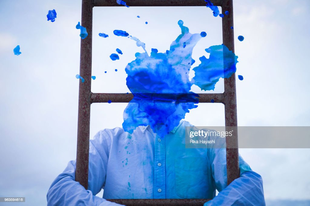 A man who became a blue painting face climbing a ladder : Stock Photo