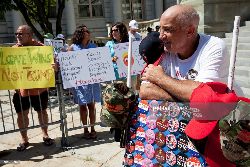 A man who declined to be named sells Trump gear as protestors of Republican Presidential candidate Donald Trump line up at the Merrill Auditorium on August 4, 2016 in Portland, Maine.