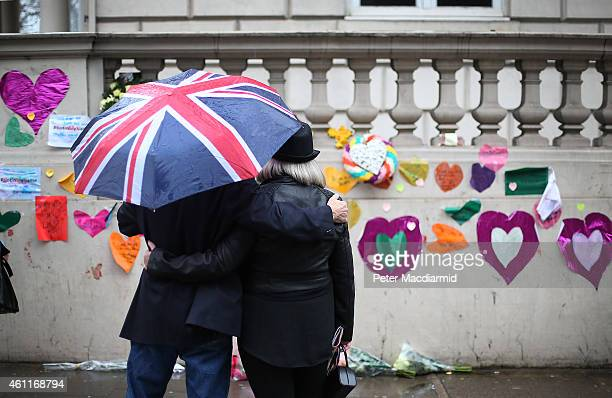 A man who had just placed a pair of pencils and a note offering sympathy to the victims of the Paris shootings on a wall at the French Embassy stands...