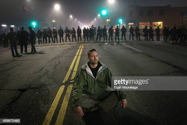 A man who identified himself as Mike V sits in the street after being blocked by a line of police officers on the second night of demonstrations...