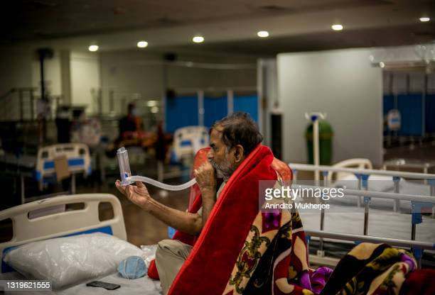 Man who is Covid-19 coronavirus positive performs a breathing exercise using a tool by blowing air into it inside a Covid Care center inside a...