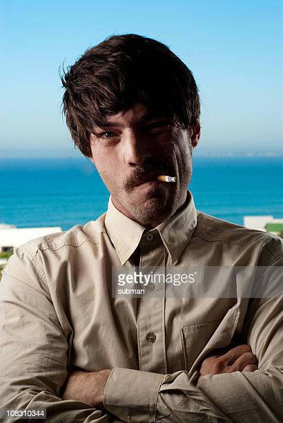 A man who is smoking by the ocean