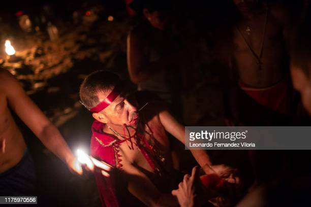 A man who is trance by a spirit of a viking warrior prepares to heal a person following the cult of María Lionza during a spiritual ritual in a...