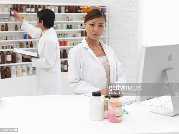 Man who looks for medicine from shelf with woman