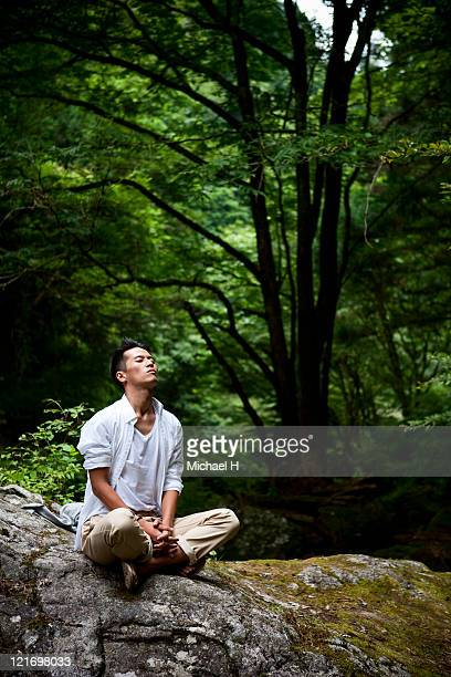 Man who meditates on rock