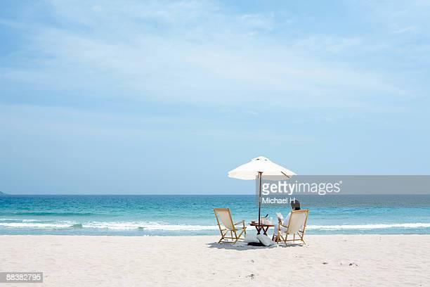 Man who reads under parasol put on beach