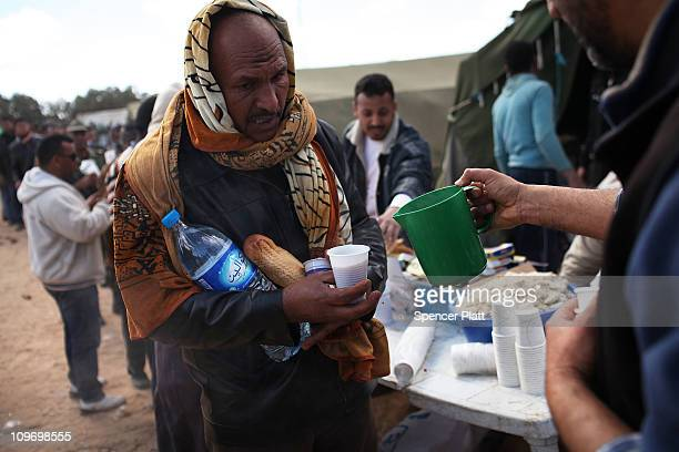 A man who recently entered into Tunisia from Libya is given food at a transit camp on March 01 2011 in Ras Jdir Tunisia As fighting continues in and...