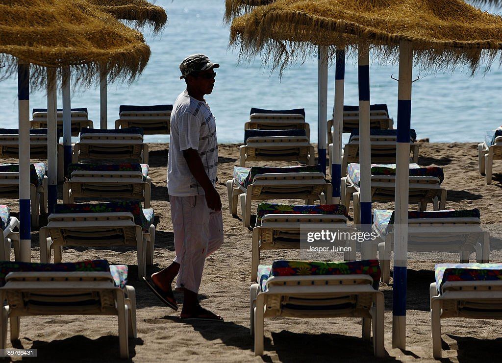 A man who rents sunbeds waits for tourists at a usually packed Costa del Sol Carihuela beach on August 13, 2009 in Torremolinos, Spain. Altough Spanish resorts remain busy, receiving 23.6 million foreign visitors in the first half year, the economic downturn has seen more than an eleven percent drop in visitors, especially from Britain, over the same period as last year. European holidaymakers are increasingly staying at home for their annual holidays.