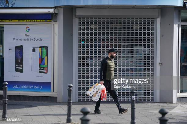 Man, who said he did not mind being photographed, carries packages of toilet paper as he walks past a shop shuttered following a city ordinance...
