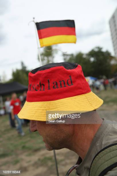 A man who said he did not mind being photographed wearing a hat in the colors of the German flag attends a gathering hosted by the Identitarian...