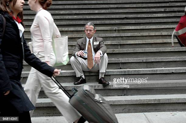 A man who says he's been a trader at the New York Stock Exchange for 25 years but declined to give his name sits on the steps of The Federal Hall...