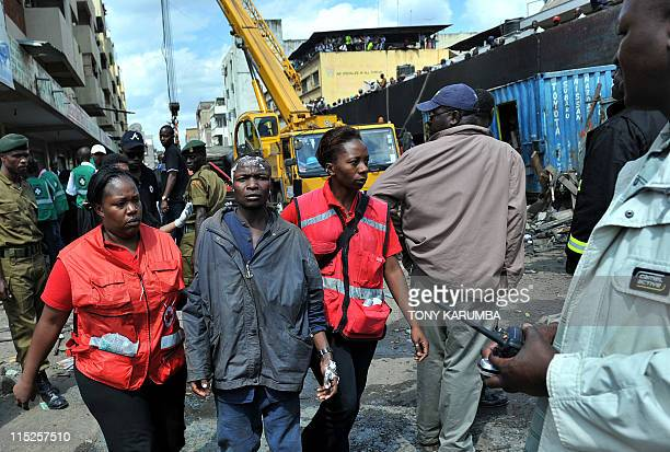 A man who sustained injuries to his head is led away by medical staff as Kenyan police fire crews and emergency workers clear debris from the scene...