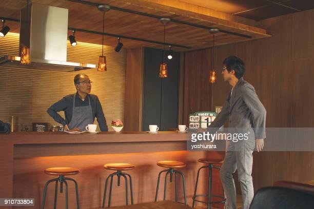 日本のカフェで、マスターと話す人