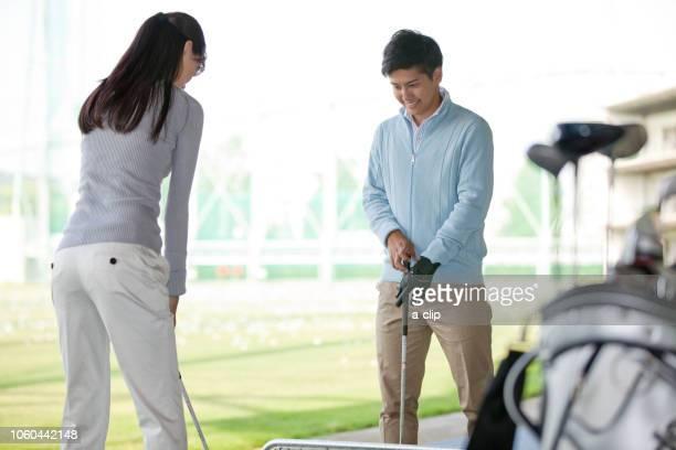 女性にゴルフを教える男性 - ゴルフ練習場 ストックフォトと画像