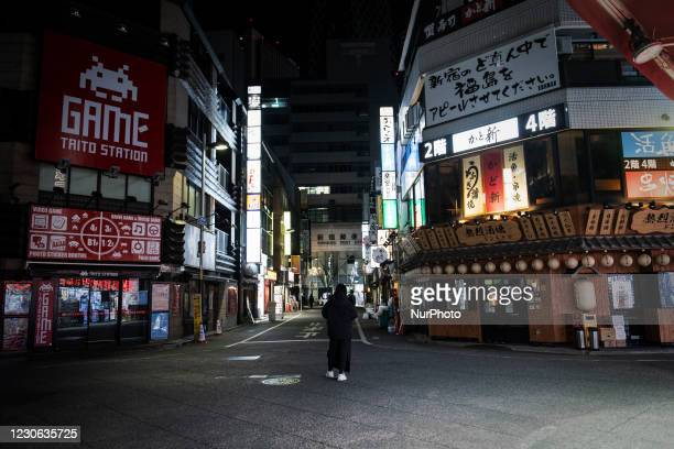 Man who tout for a bar stands deserted street after 8 p.m. In Tokyo, Japan on 11 January 2021.